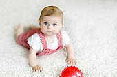 Cute baby girl playing with red gum ball.