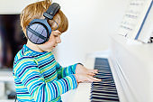 Cute healthy little kid boy playing piano in living room or music school. Preschool child having fun with learning to play music instrument. Education, skills concept