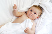 Cute little baby playing with own feet after taking bath. Adorable beautiful girl wrapped in white towels