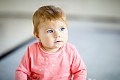 Portrait of cute baby girl at home. Little girl looking at the camera and smiling. Family, new life, childhood, beginning concept