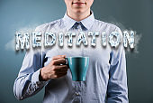 Casual businesswoman holding cup of coffee/tea with smoke text MEDITATION / Blue background (Click for more)
