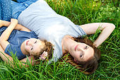 Beautiful young mother and little daughter sitting on green grass and resting
