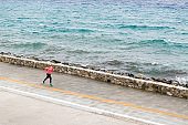 Woman running on city street at seaside