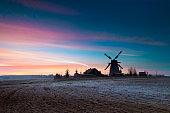 Frosted autumn sunrise behind wooden windmill in Dudutki village, Minsk, Belarus