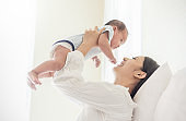 Portrait of mother lifting and playing with newborn baby, baby talking to mother. Health care family love together