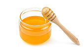 Honey pot and dipper isolated on white background as package design element.