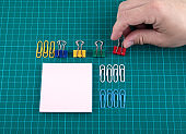 Paper clips and note sheet on checked green background