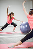 Athletic Female Pilates Training With Fitness Ball In Gym