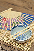 Chinese bowl, chopsticks and a blue hand fan