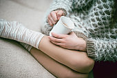 Female Wearing Sweater and Drinking Tea On Sofa