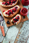 Healthy snack, jam on toasts. Raspberry jam, ricotta and raw berries on ciabatta bread on rustic blue background above view