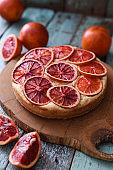 Homemade fruit cake. Blood orange cake with raw organic oranges on oak board
