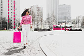 A fashionable and modern woman is walking with shopping.