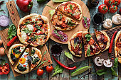 Flatlay of abundant pizza party. Rustic homemade pizzas with salami, eggs and vegetables served with red wine and raw vegetables on shabby wooden background