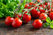 Fresh red cherry tomatoes with basil on a rustic wooden background