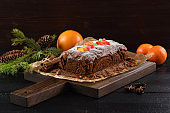 Tasty traditional fruit cake in baking paper decorated with candied fruits, clementines and fir branch on dark background