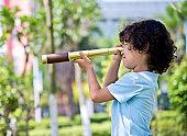 Little boy holding a telescope at park