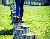 Woman walking on stepping tree stump