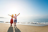 Couple standing on the beach with arms raised