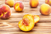 Halves of peaches with whole peaches on wooden background.