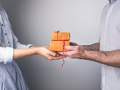 Handsome man giving a gift to his beloved woman