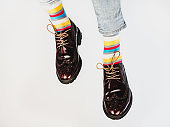 Men's legs in bright, striped, multi-colored socks