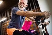 Happy senior people doing indoor biking in a fitness club