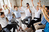 Business, startup, gesture, people and teamwork concept - happy creative team in office