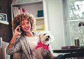 Businesswoman working at home office and holding her puppy