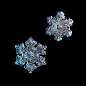 Two snowflakes isolated on black background