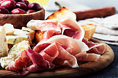 Snacks or antipasti, crostini, prosciutto, blue cheese and olives