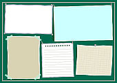 Colorful paper notes with pins and adhesive tape on green background.