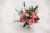 Winter wedding concept. Bouquet of fresh flowers in white snow