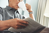 Asian senior man reading newspaper.