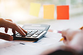 Close up woman using calculator and writing make note with calculate about cost at home office.