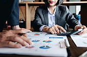 Teamwork of business two colleagues analysis with financial data and marketing report graph, Young co worker discussing for calculating financial document with calculator