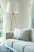 Comfortable sofa with pillows and standing lamp in the living room