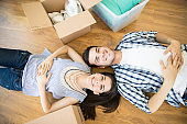 Happy Couple Lying By Boxes On Floor In New Home