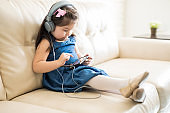 Little girl listening to music on a cell phone