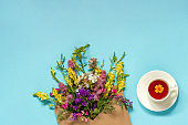Field flowers in craft envelope and cup of herbs tea