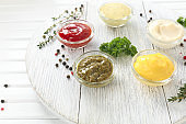 Different tasty sauces in bowls on white wooden board