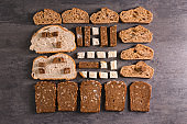 Flat lay composition with slices of freshly baked bread on gray background