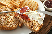 Spreading jam on toasted bread with creme cheese, closeup