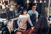 Asia barista waiter and waitress take order from customer in coffee shop,Two cafe owner writing drink order at counter bar,Food and drink business concept,Service mind concept.