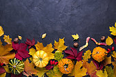 Autumn composition. Frame made of different multicolor dried leaves and pumpkin on dark background. Autumn, fall concept. Flat lay, top view, copy space