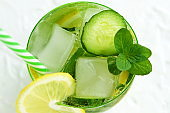 Glassware with refreshing lemon, cucumber and mint fruits cocktail, detox water on white  background
