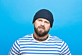 Portrait of angry bearded sailor against ble background