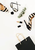 Flat lay, top view of female fashion accessories.Beige handbag, sunglasses, high heel shoes and cosmetics on white background. Copy space