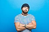 Portrait of confident bearded sailor against ble background