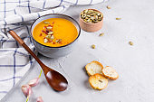 Pumpkin cream soup with seeds, toast and seasoning in a ceramic bowl on a table. Copy space